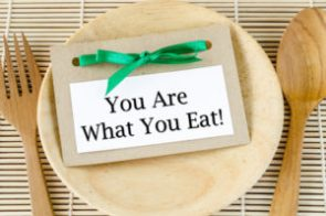 46125447 - healthy lifestyle concept - you are what to eat reminder words in paper tag on dish and spoon wooden.