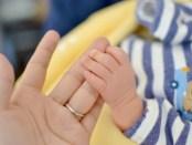 母の手を握る赤ちゃん