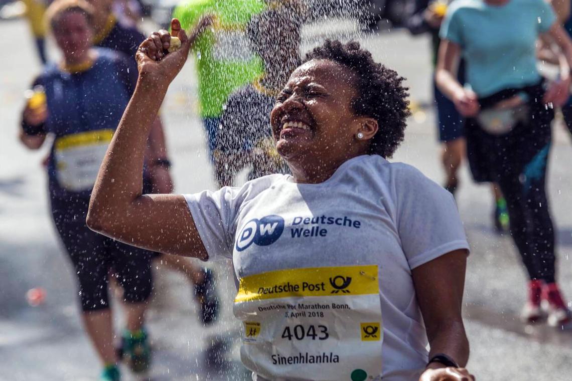 Sine Buthelezi nimmt eine kleine Wasserdusche beim Marathon in Bonn