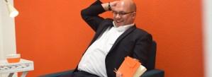 Oliver lacht, im Sessel, vor orangener Wand im menschmark-Büro