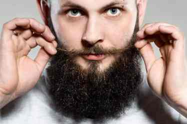Man growing a beard and grooming his mustaches