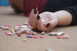 Coloured image of white female lying on the floor with tablets all around her