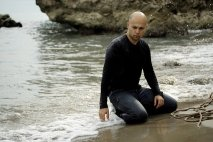 Coloured image of bald young man kneeling on the beach with a noose beside him