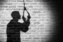 Black and white image showing shadow of a man holding a noose that's hanging down - male suicide?