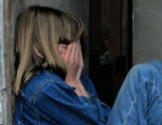 Girl with long blond hair wearing blue denim jacket and jeans. Sitting, leaning against a wall and covering her face