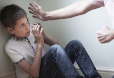 Young boy wearing blue jeans and white t-shirt. Sitting on the floor with his hand up defending himself as females hand that look like they're about to hit or slap