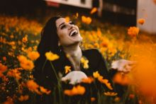 Lady with long dark hair sitting in a field of yellow sunny flowers, arms out wide, smiling