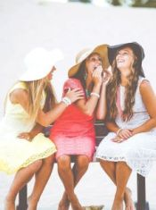The young women in sun hats and summer dresses, laughing