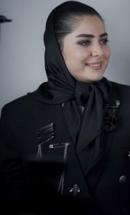 Colour image lady in black jacket and scarf covering most of her hair