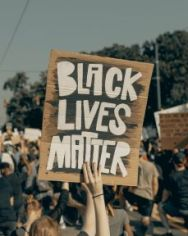 Colour image of protest and placard saying Black lives matter