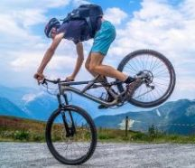 Colour image a man wearing blue t shirt and shorts on a cycle with back wheel up in the air