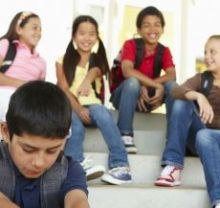 Four multi racial children sitting on steps laughing at another little boy - excluding him, which is social bullying