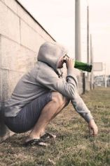 Grey scale image of man in hoody and shorts, sitting down leaning on his haynchesagainst a wall drinking from bottle