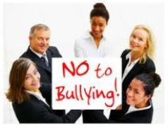 Five people all wearing suits, standing in a circle hold a white poster with red writing - says No to bullying