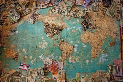 travelling mementos: world map with pins and currencies