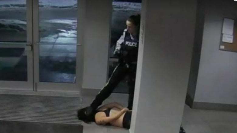RCMP Cst. Lacy Browning with her foot on Mona Wang's head during a wellness check