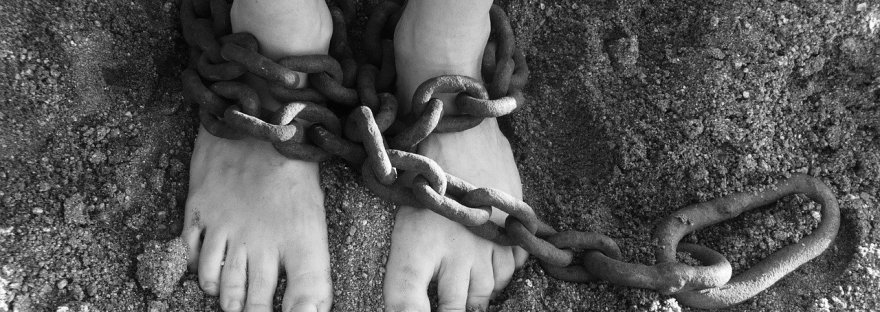 chain wrapped around ankles of person standing in sand
