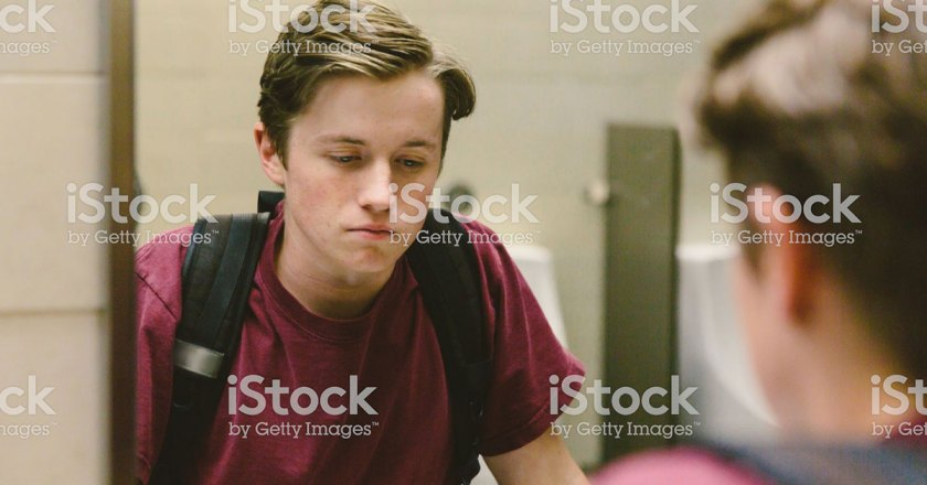 young man looking in mirror introspectively