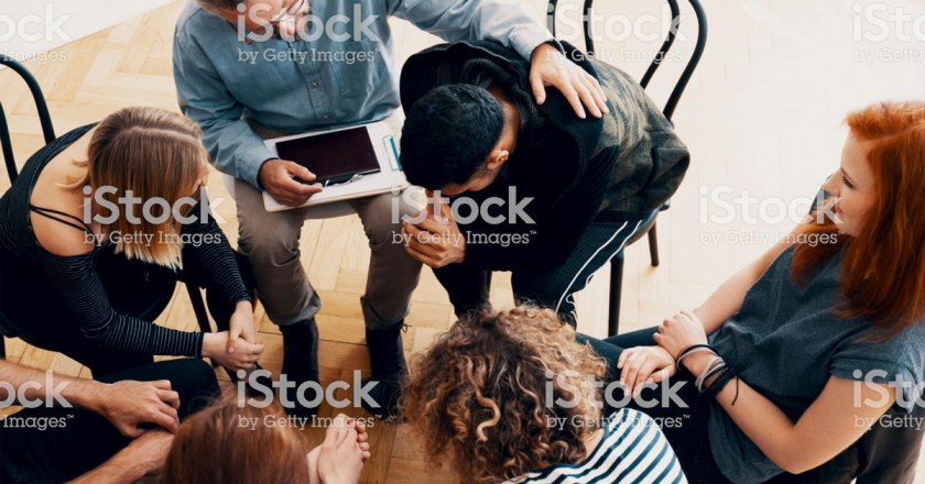 counselor comforting man in group therapy setting