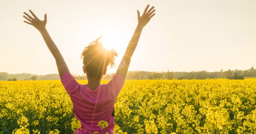 woman raising her hands in the sunset