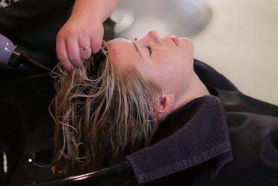 シャンプー後にマッサージをしている女性