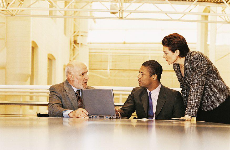 Three people gathered around a computer