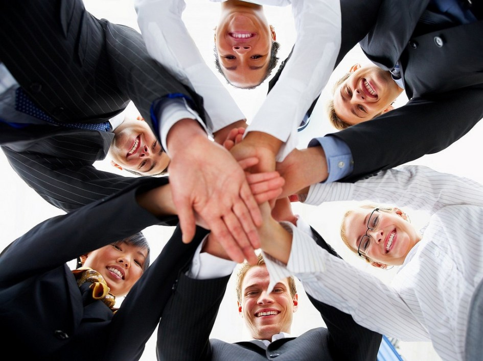 six people with their hands in a huddle.