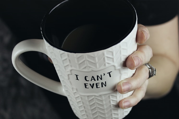 "Woman holding a mug with ""I can't even"" written on it."
