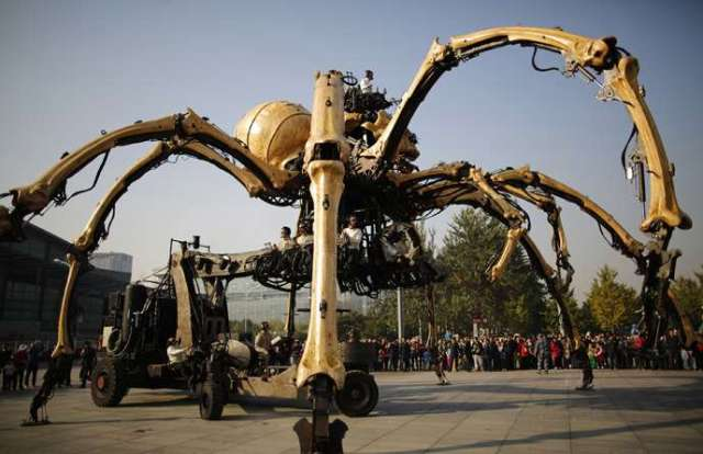 """People watch a mechanical installation named """"The Spider""""  make its way during the Long Ma performance in front of the National Stadium, also known as the Bird's Nest, in Beijing"""