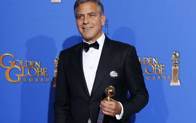 Honoree actor George Clooney poses with the Cecille B. DeMille award backstage at the 72nd Golden Globe Awards in Beverly Hills