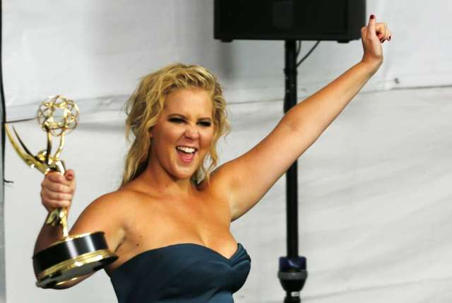 """Comedian Amy Schumer enters the photoroom with her award for Outstanding Variety Sketch Series for Comedy Centrals' """"Inside Amy Schumer"""" during the 67th Primetime Emmy Awards in Los Angeles, California September 20, 2015. REUTERS/Mike Blake - RTS230F"""