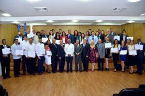 Graduandos y graduandas muestran sus certificados acompañados del ministro Santana, del rector de Intec, y de las demás autoridades gubernamentales y académicas.