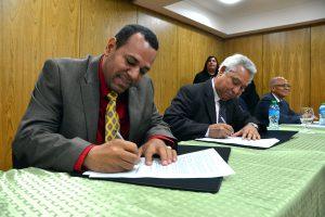 Acto de firma del convenio de inducción a la inversión pública entre el ministro de Economía, Isidoro Santana, y el alcalde de Tamboril y secretario general de la Federación de Municipios (FEDOMU), Anyolino Germosén León.