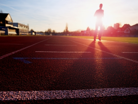 74740534 - tall man running on red running racetrack on the stadium. sportsman in training clothes at amazing sunset. sport and healthy lifestyle concept and jogging civic training workout