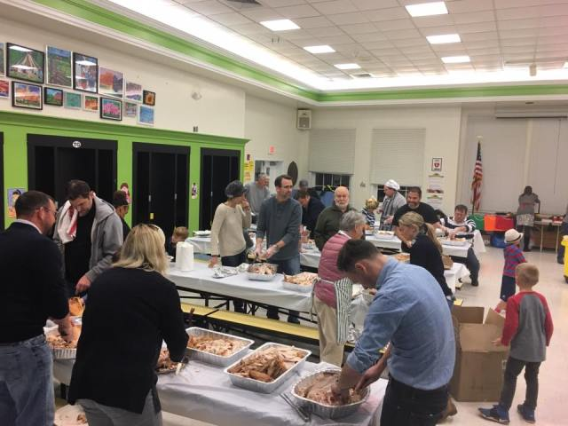 Caption (2): Parents and students came together in the Toll Gate cafeteria Tuesday evening to carve and package 60 turkeys as part of the school's effort to prepare Thanksgiving dinner for the Trenton Area Soup Kitchen.