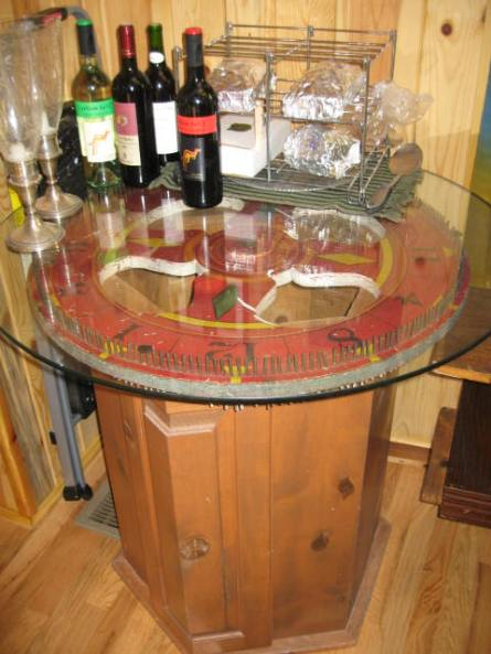 A carnival wheel made into a glasstop table. I also mix and match bases with large tractor gears as the main focus of the table.