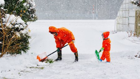 father and son shoveling snow in orange jackets
