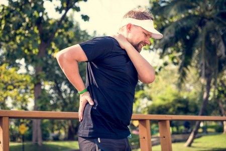male golfer wearing visor experiencing back pain