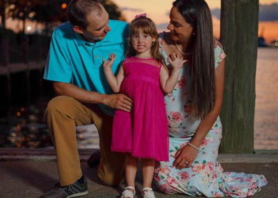 Very excited little girl telling parents how happy she is about her soon to be new baby sister at sunset maternity and family session in Norfolk, VA