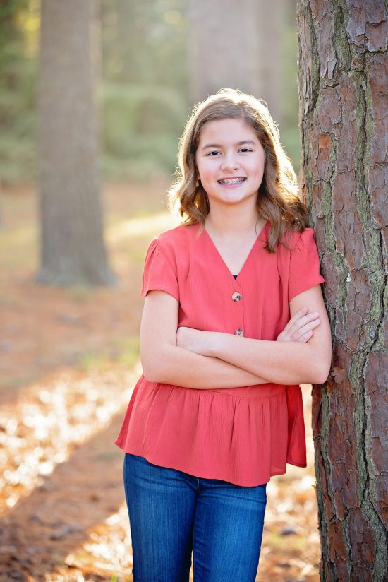 Young girl wearing red top leaning up against tree