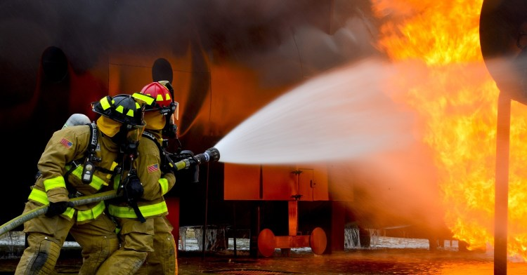 Firefighters putting out a fire with a hose