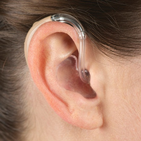 Close up of ear with a BTE hearing aid inserted