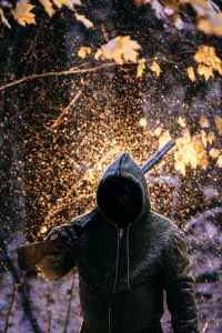 man wearing jacket carrying a gun