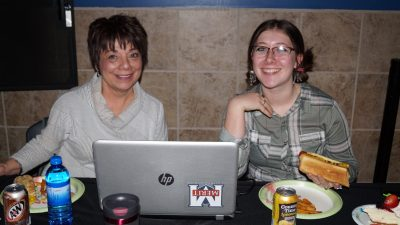 two women with a laptop smiling