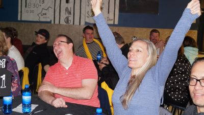 Man and woman sitting at game table smiling and cheering