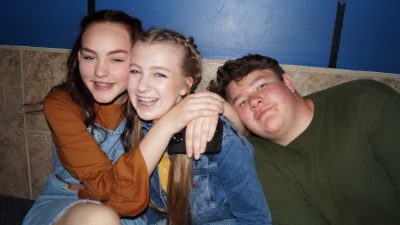 Three teens smiling and hugging