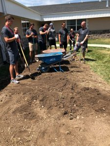 men hauling dirt and grass at merit academy