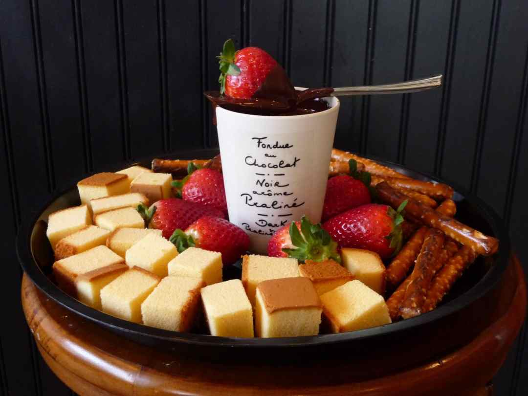Easy chocolate fondue recipe with fruit, cake and pretzels