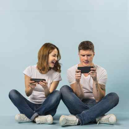 Young-couple-enjoying-the-video-game-on-cellphone-against-blue-backdrop