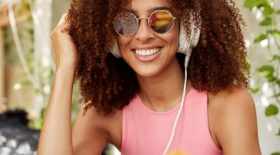 happy-dark-skinned-curly-female-model-trendy-shades-enjoys-music-big-headphones-has-shining-smile-listens-radio-beautiful-african-female-listens-favourite-broadcast-with-earphones.jpg